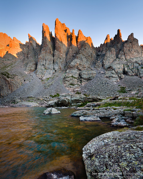 The glow of the sunrise hitting the awesome Cathedral Spires in RMNP is reflected in Sky Pond.